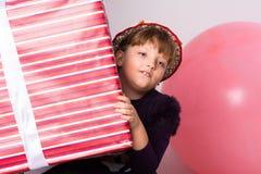 Adolescente pensativo con una caja de regalo Imagen de archivo libre de regalías