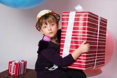 Adolescente pensativo con una caja de regalo Imágenes de archivo libres de regalías