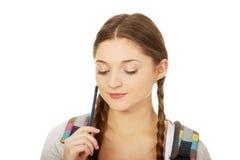 Adolescente pensativo con una pluma Foto de archivo