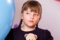 Adolescente pensativo en bola de goma grande azul Fotografía de archivo