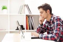Adolescente pensativo en el ordenador Imágenes de archivo libres de regalías