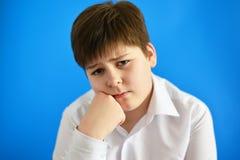 Adolescente pensativo en fondo azul Foto de archivo