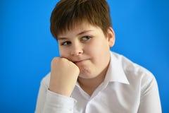 Adolescente pensativo en fondo azul Fotos de archivo