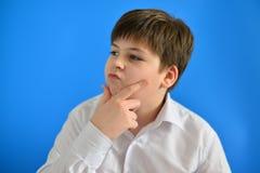 Adolescente pensativo en fondo azul Imágenes de archivo libres de regalías