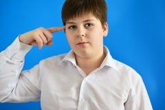 Adolescente pensativo en fondo azul Imagen de archivo
