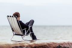 Adolescente pensativo en su silla que hace frente en el océano Foto de archivo