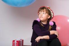 Adolescente pensativo en un sombrero que se sienta con un regalo Imagen de archivo