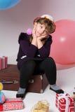 Adolescente pensativo en un sombrero que se sienta en una maleta Imagen de archivo