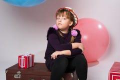 Adolescente pensativo en un sombrero que se sienta en una maleta Fotografía de archivo