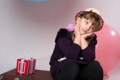 Adolescente pensativo en un sombrero que se sienta en una maleta Fotos de archivo libres de regalías