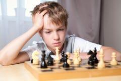 Adolescente pensativo que juega a ajedrez Fotos de archivo libres de regalías