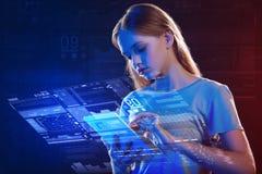 Adolescente pensativo que mira la tableta y que hace un holograma Imagen de archivo