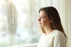 Adolescente pensativo que mira a través de una ventana Fotos de archivo