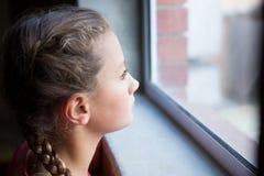 Adolescente pensativo que mira a través de ventana Fotos de archivo libres de regalías