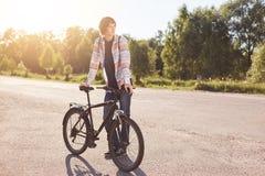 Adolescente pensativo que se coloca en el camino, guardando la mano en la barra de la manija de su bici, esperando otras ciclista Fotos de archivo