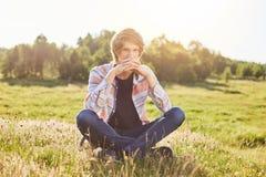Adolescente pensativo que se sienta al aire libre en el campo que admira los paisajes pintorescos que piensan en algo con la expr Fotografía de archivo