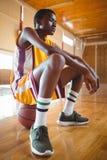 Adolescente pensativo que se sienta en baloncesto Imagen de archivo libre de regalías