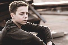 Adolescente pensativo que se sienta en el tejado de la casa Imagen de archivo