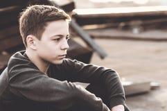 Adolescente pensativo que se sienta en el tejado de la casa Foto de archivo libre de regalías