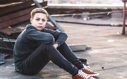 Adolescente pensativo que se sienta en el tejado de la casa Fotografía de archivo