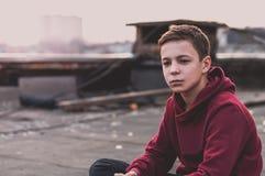 Adolescente pensativo que se sienta en el tejado de la casa Imágenes de archivo libres de regalías