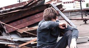 Adolescente pensativo que se sienta en el tejado de la casa Fotografía de archivo libre de regalías