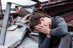 Adolescente pensativo que se sienta en el tejado de la casa Foto de archivo