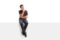 Adolescente pensativo que se sienta en un panel Fotografía de archivo libre de regalías