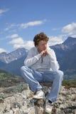 Adolescente pensativo que se sienta en una pared Fotos de archivo