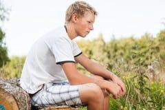 Adolescente pensativo que se sienta en una pila de madera Imagenes de archivo