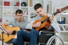 Adolescente perjudicado que toca la guitarra con el amigo Imagen de archivo