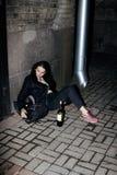 Adolescente pobre joven que se sienta en la pared sucia en piso con la botella de vid, alcohólico pobre del refugiado, desamparad Fotografía de archivo libre de regalías