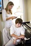 Adolescente por el piano con la hermana texting Foto de archivo libre de regalías