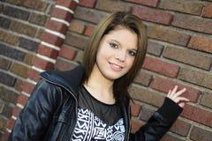 Adolescente por uma parede de tijolo Fotografia de Stock Royalty Free