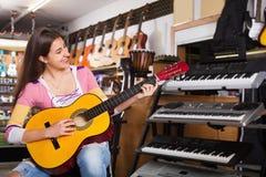 Adolescente positivo alegre que presenta con la guitarra clásica Fotografía de archivo