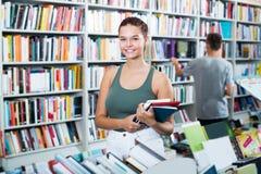 Adolescente positivo de la muchacha que sostiene los nuevos libros en manos Fotos de archivo libres de regalías