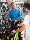 Adolescente positivo del hombre y del muchacho que escoge la nueva bicicleta Imagenes de archivo