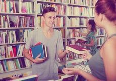 Adolescente positivo del muchacho que toma el nuevo libro del vendedor Foto de archivo