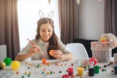 Adolescente positivo felice che prepara per Pasqua Si siede da solo alle uova della pittura e della tavola Sorriso della ragazza  fotografia stock