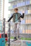Adolescente positivo lindo del muchacho en el patio en la ciudad solamente imagen de archivo
