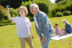 Adolescente positivo que está alegre mientras que juega con el avión de papel Foto de archivo