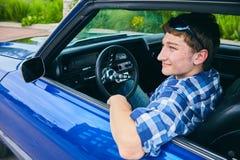Adolescente positivo que se sienta en coche y la sonrisa Fotos de archivo