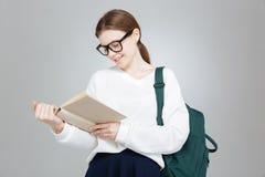 Adolescente precioso alegre en vidrios con el libro de lectura de la mochila Fotos de archivo libres de regalías