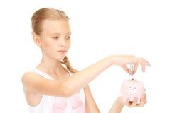 Adolescente precioso con la hucha y el dinero Imagen de archivo