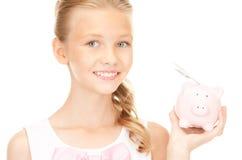 Adolescente precioso con la hucha y el dinero Imagenes de archivo