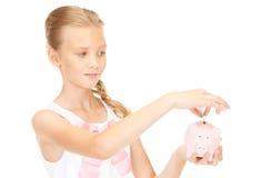 Adolescente precioso con la hucha y el dinero Imagen de archivo libre de regalías