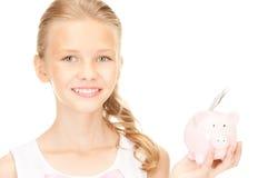 Adolescente precioso con la hucha y el dinero Foto de archivo