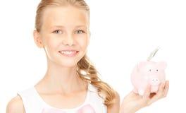 Adolescente precioso con la hucha y el dinero Fotos de archivo libres de regalías