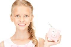 Adolescente precioso con la hucha y el dinero Fotografía de archivo