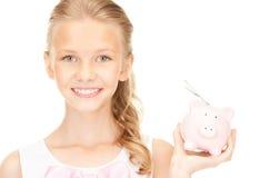 Adolescente precioso con la hucha y el dinero Fotografía de archivo libre de regalías